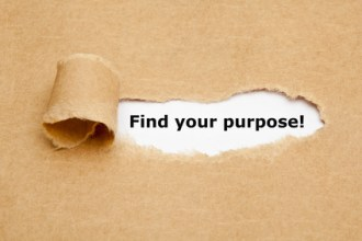 """Find your purpose"" appearing behind torn brown paper."
