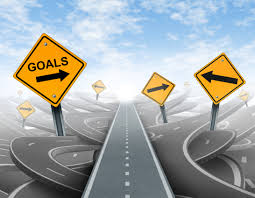 Goals sign post on side of road with arrows pointing the way