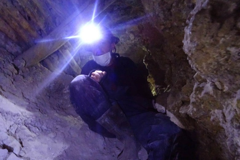 Not for the claustrophobic: climbing down a narrow rocky shaft deep in the mountain