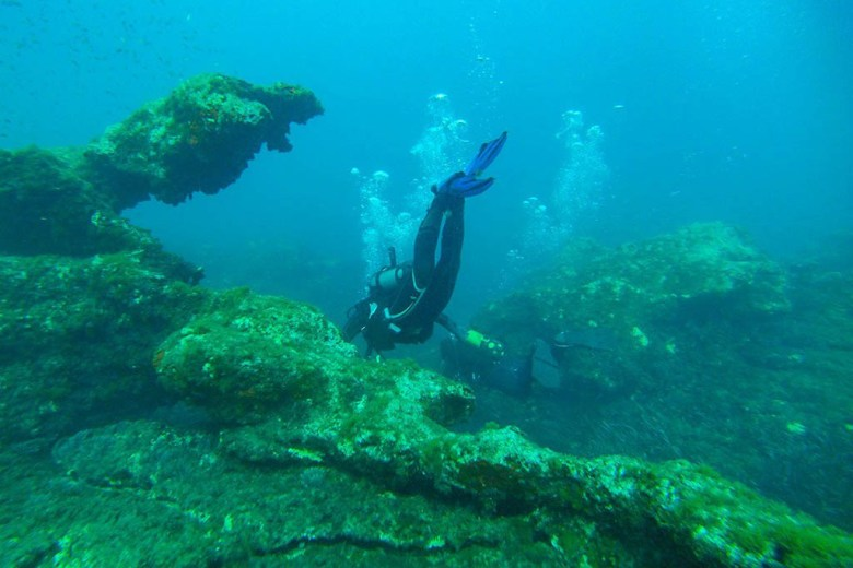 Exploring rock formations in Sliema Bay while diving in Malta