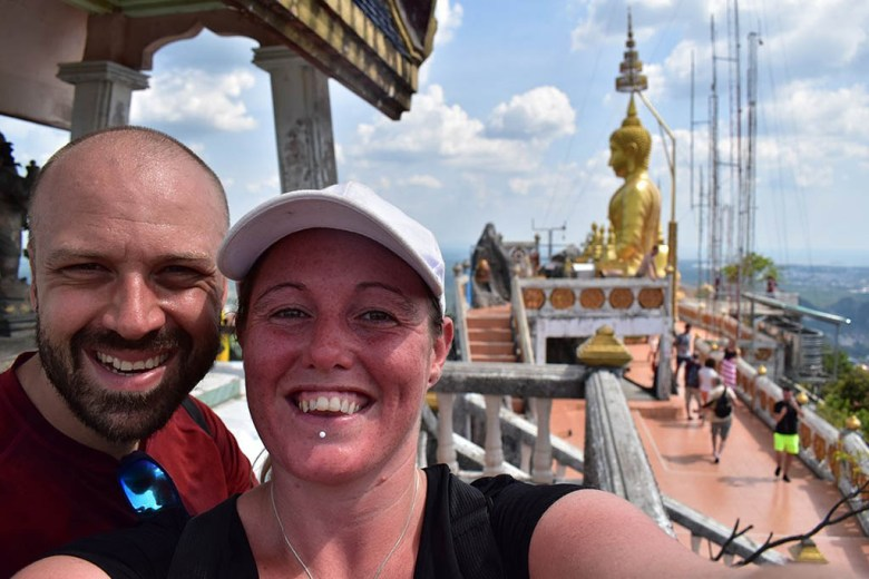 Enjoying the moment at the top of Tiger Cave Temple, with the golden Buddha statue in the background