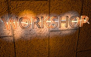 Glowing sign on cinder block background that says workshop.