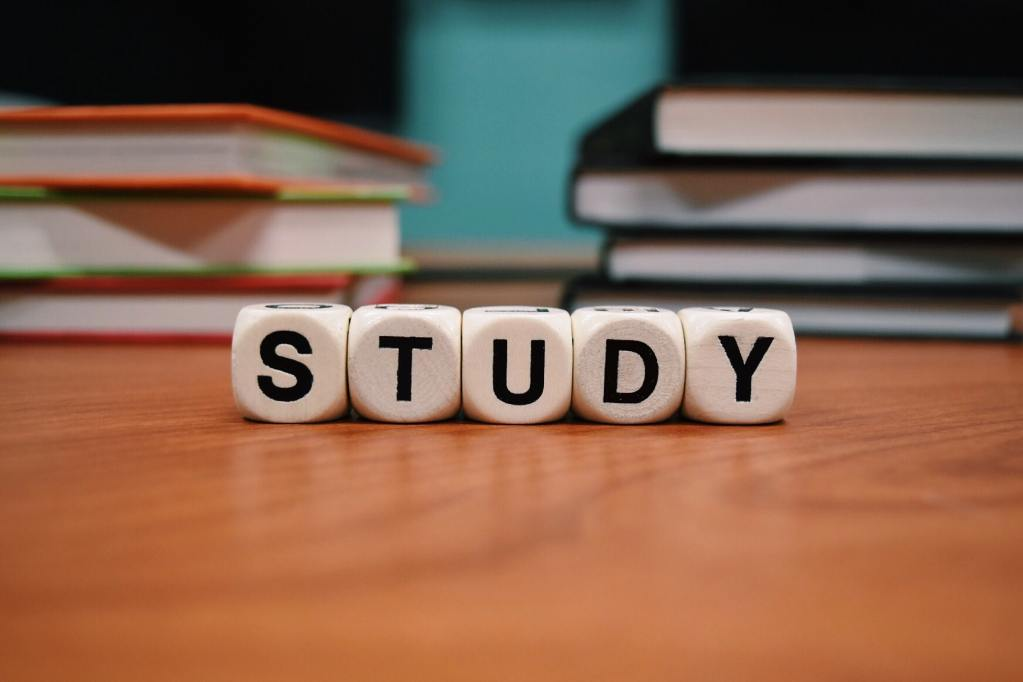 """The word """"study"""" is spelled out in wood blocks on a desk with books in the background."""