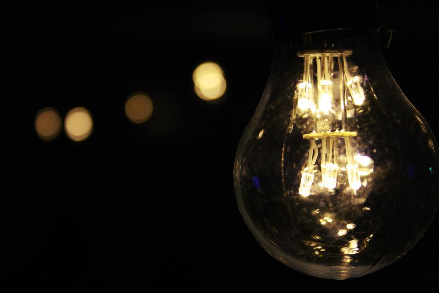 Lighted bulb in the dark. Photo by Nita from Pexels