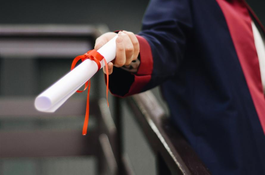 Arm in graduation robe handing out a credential rolled and tied with red ribbon.