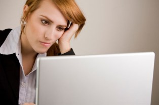 Young woman looking at a laptop computer and appearing very frustrated.
