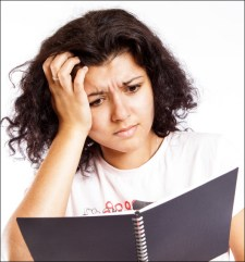 A young lady looking at a paper and appearing very confused about its content.