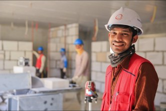 Young man in a job setting wearing a hard hat and safety vest.