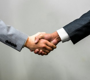 Close-up of the arms of two individuals in business suits shaking hands; one white and one of color.