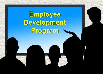 """Classroom setting with silhouettes of presenter and attendees. Screen on wall reads """"Employee Development Program."""""""