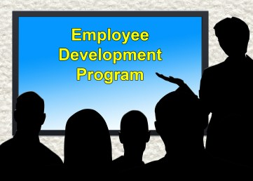 "Classroom setting with silhouettes of presenter and attendees. Screen on wall reads ""Employee Development Program."""