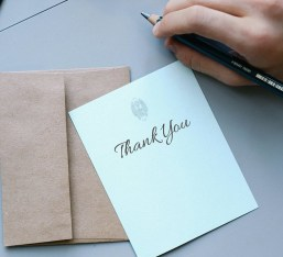 A thank-you card with an envelope and a hand holding a pencil.