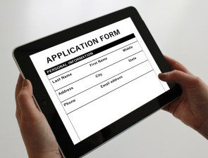 Hands holding an iPad which displays an online job application form.