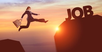 """Businesswoman jumping from one rock up to another, with the word """"job"""" as the goal."""