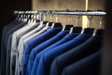 The interior of a closet showing several suit coats of various colors.