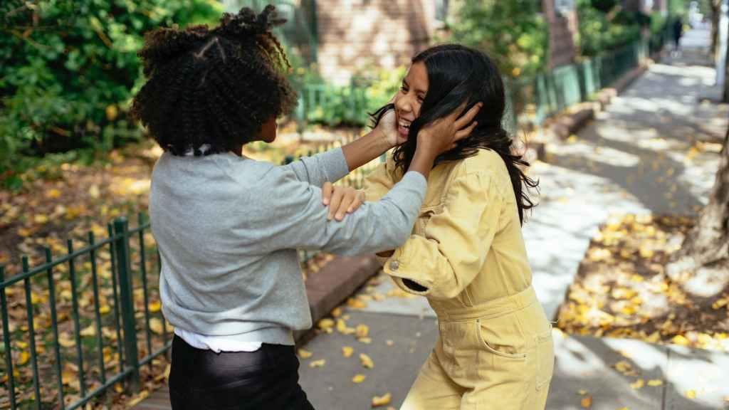 unrecognizable happy multiethnic girls having fun on urban walkway