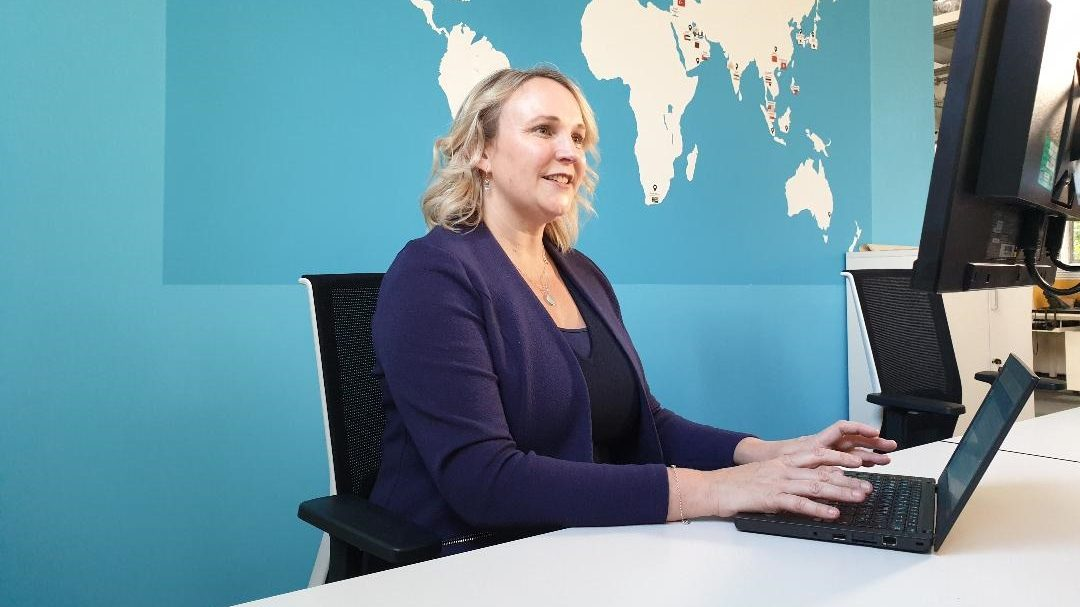 A woman types at a computer in professional attire