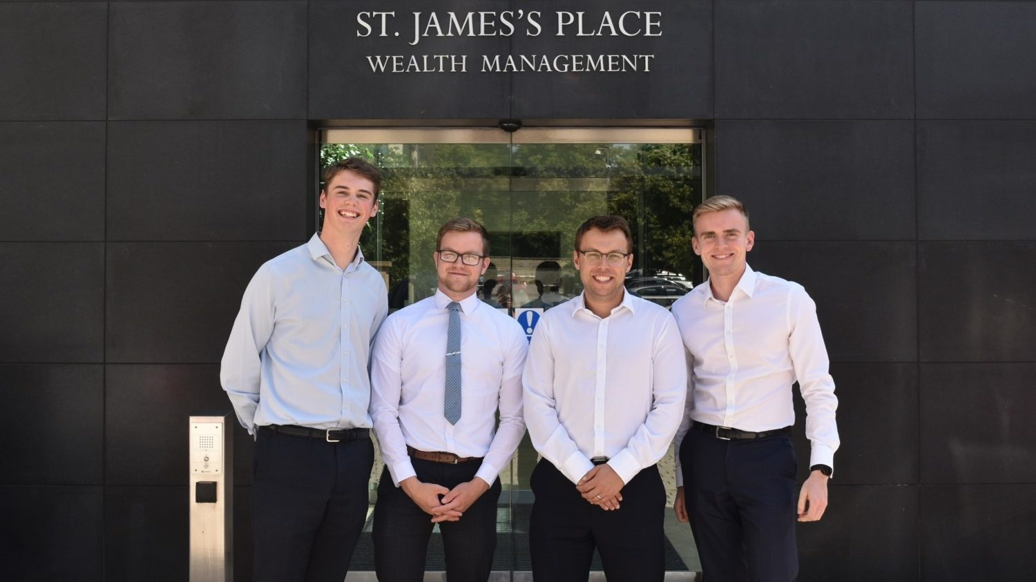 4 professional looking men stand outside of a building that says St James's Place Wealth Management