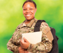 A smiling woman in military fatigues wearing a backpack and holding a binder