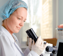 An older woman in gloves and a hairnet using a microscope