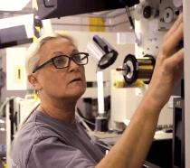 An older woman running a manufacturing machine