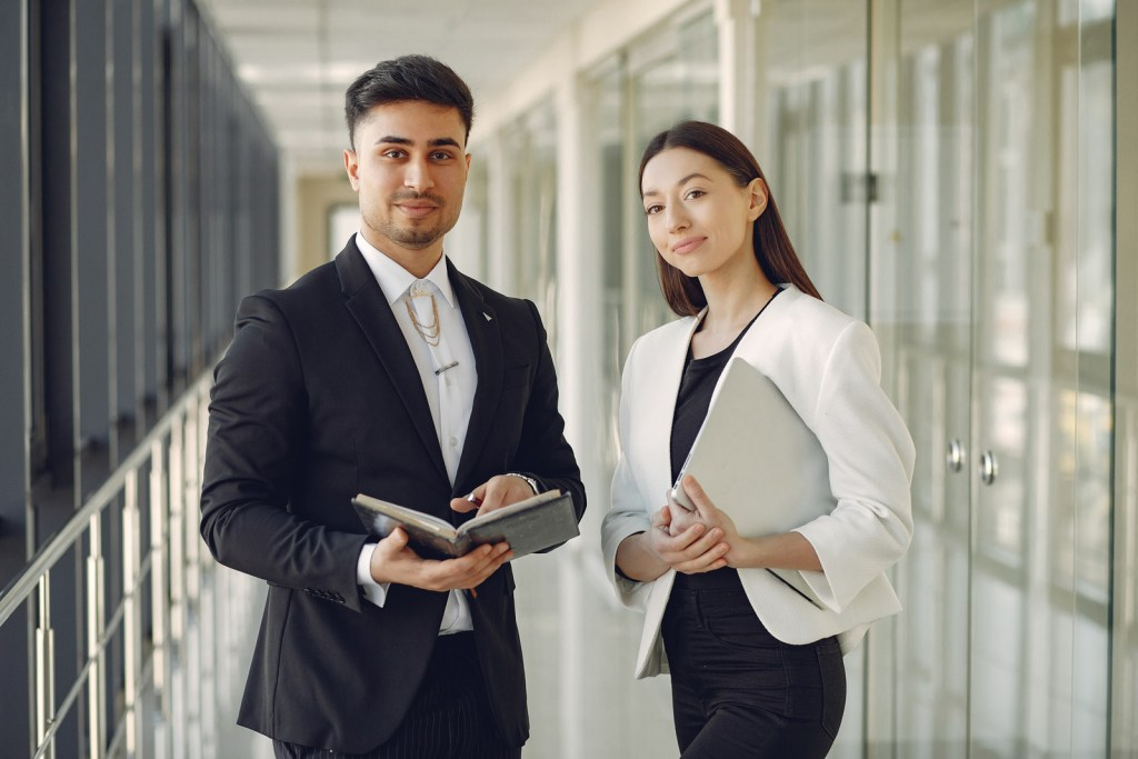 Two professional business people standing and looking at the camera. One man and one woman.