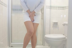 woman holding her crotch and standing in front of the toilet bowl