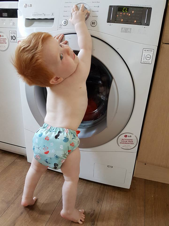 a young toddler standing in front of a washing machine wearing just a cloth nappy