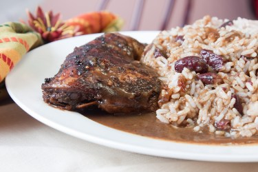 Caribbean style jerk chicken served with rice mixed with red kidney beans. Shallow Focus on the chicken.