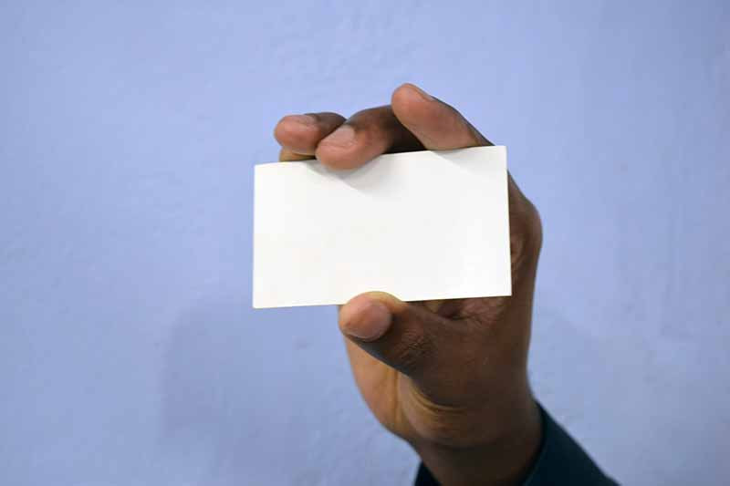 Black hand holding blank business card on blue background ...
