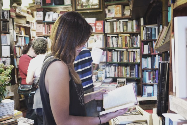 Carina Behrens leser i en bok i Paris. Carinabehrens.com