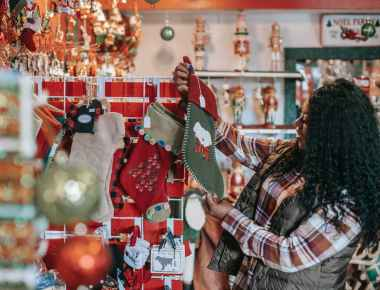 smiling black woman choosing christmas decorations in store
