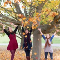 Three friends throwing leaves in the air