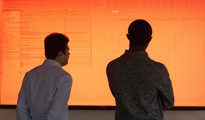 Two men, silhouetted, looking at a glowing orange spreadsheet on a massive screen in the background