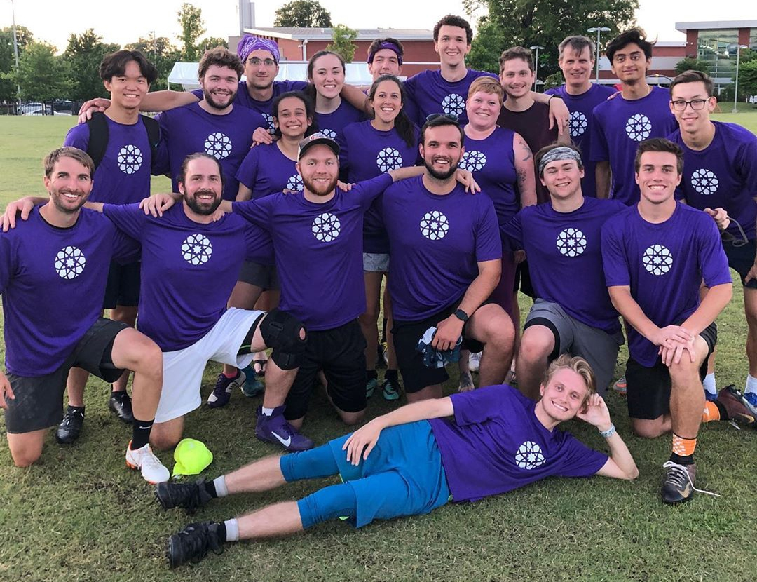 Large group of ultimate frisbee players wearing purple jerseys showing the MUDA icon