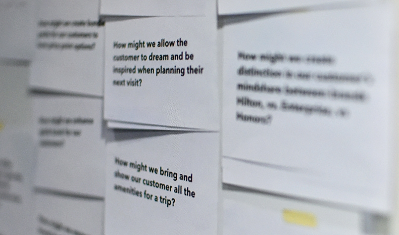 Soft focus photo of pieces of paper with questions related to Hilton.com customers taped to a wall