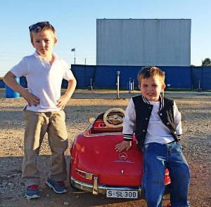 Two kids and a toy car in front of a drive-in screen