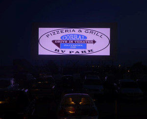 Corral Drive-In logo projected on its screen at night