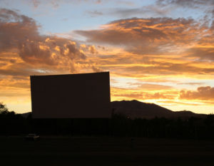 El Rancho Drive-In screen silhouetted in a colorful sunset