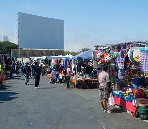 Daytime swap meet with drive-in screen in background