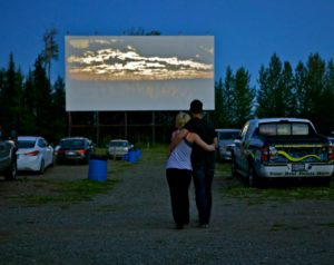 Couple hugging in front of a drive-in screen at twilight