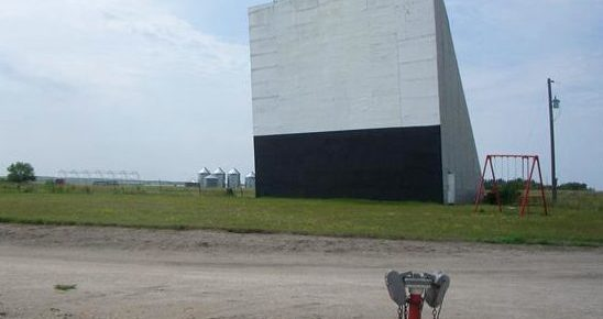 Twilight Drive-In screen with old-style speakers in the foreground