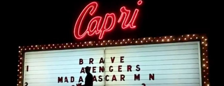 Worker changing letters on the Capri Drive-In marquee at night