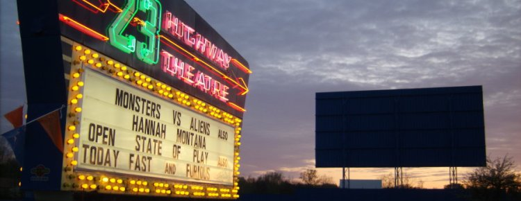 US 23 neon marquee and screen silhouetted at sunset