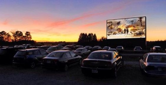 Cars in front of a drive-in screen after sunset