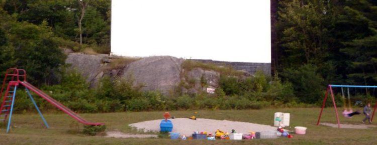Muskoka Drive-In screen on a rock with playground equipment in front