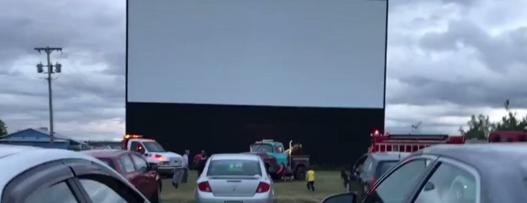 Drive-In screen with cars on a cloudy evening