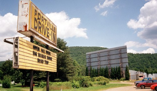 Portville Drive-In sign with its main screen in the background