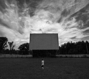 Black and white photo of the screen with streaked clouds behind it