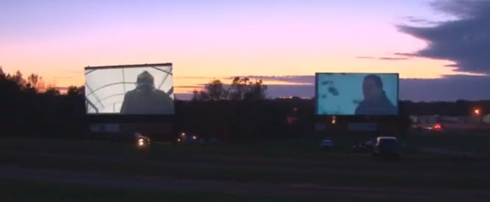 Two drive-in screens showing movies at twilight